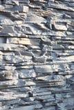 Vägg av den dekorativa stenen i grå färger Grunt djup av fältet, abstrakt bakgrund Arkivfoto