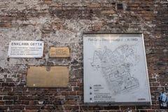 Vägg av den historiska judiska gettot i Warszawa Polen och att visa plattor och översikten av gettot på väggen royaltyfria bilder