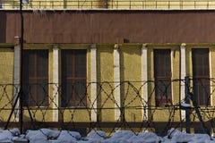 Vägg av en industribyggnad bak ett staket med försett med en hulling - tråd fotografering för bildbyråer