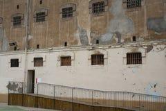 Vägg av fängelsebyggnad med fönster av priconceller royaltyfri foto