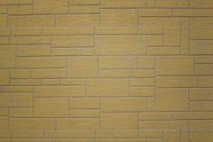 Vägg av gråa gula tegelplattor av olika format och former Textur f?r grov yttersida arkivbilder