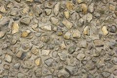 vägg av gula och vita stenar av olika format och former i grått cement Textur för grov yttersida royaltyfria foton