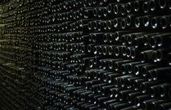 Vägg av källaren mycket av gamla vinflaskor arkivbild