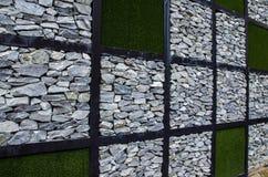 Vägg av stenen och konstgjort gräs arkivbild