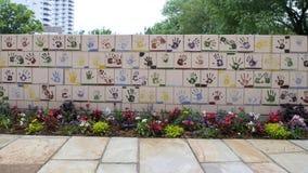 Vägg av tegelplattor som göras av barn, framdel av den nationella minnesmärken för oklahoma city & museum, med blommor i förgrund Arkivbild