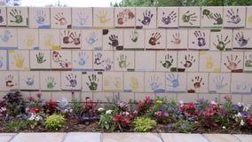 Vägg av tegelplattor som göras av barn, framdel av den nationella minnesmärken för oklahoma city & museum, med blommor i förgrund Royaltyfri Bild