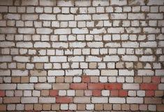 Vägg av vita och röda tegelstenar med det ojämna gamla murverket arkivbild