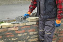 Vägg för arbetarbyggnadstegelsten genom att använda mursleven Arkivbild