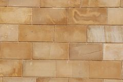 Vägg för grov yttersida för kvarter för gul tegelsten för buseyttersida naturlig gammal naturlig royaltyfria bilder