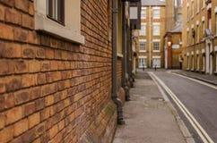 Vägg för röd tegelsten av byggnaden i den stads- engelska byggnaden som är ty Arkivfoto