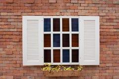 Vägg för röd tegelsten med det vita fönstret Arkivbild