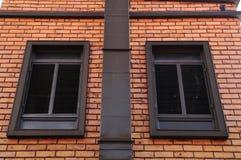 Vägg för röd tegelsten med klassiska fönster Royaltyfri Foto