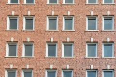 Vägg för röd tegelsten med rader av fönster Royaltyfri Foto