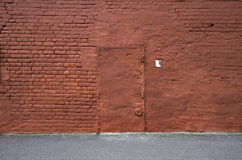 Vägg för röd tegelsten med remsan av asfalt och dörren Royaltyfria Foton