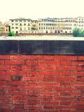 Vägg för röd tegelsten med traditionella italienska hus i bakgrunden royaltyfri fotografi