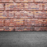 Vägg för röd tegelsten och asfaltgolv Royaltyfri Fotografi