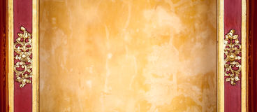 Den gula stuckaturväggen med mönstrar inramar in. royaltyfri foto