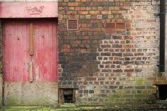 Vägg med den red ut röda dörren Royaltyfri Foto