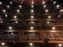 Vägg med ett stort antal balkongfönster på byggnaden Rytmen av fönstren Lyktor på balkongerna royaltyfria foton