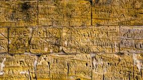 Vägg med kalkstentegelstenar med oläsliga gravyrer som har varit skriftliga vid folk med passagen av tid royaltyfri bild