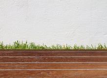 Vägg och grönt gräs på det wood golvet Royaltyfri Foto