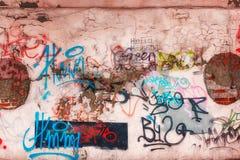 Vägg och grafitti Oläsliga inskrifter i olika färger Royaltyfri Fotografi