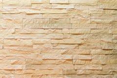 Vägg som göras av dekorativt ljus - brun sten Dekorera för spisen Bakgrund royaltyfri fotografi