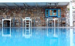 Vägg, tabeller, stolar och reflexioner i det blåa simbassängvattnet Fotografering för Bildbyråer
