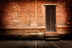 Väggar för röd tegelsten och gamla trädörrar. royaltyfri bild