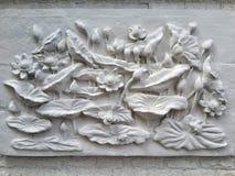 Väggbasreliefstuckaturen i murbruk, visar Lotus blommor royaltyfria bilder