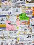 Väggen är full av annonseringar: erbjudanden av arbete och service, köp av gods, information om händelser som annonserar fotografering för bildbyråer