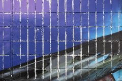 Väggen av ett bostads- hus som är dolda med tegelplattor och målar med blått- och svartmålarfärg Del av en stor grafit under det  royaltyfria foton