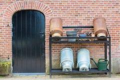 Väggen av lantgården med dörren och mjölkar cans Royaltyfri Bild