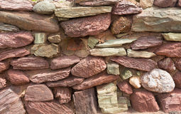 Väggen för den torra stenen med rött och rosa färger stenar den traditionella strukturen med ingen mortel Royaltyfria Bilder