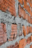 Väggen för röd tegelsten komponeras av olika tegelstenar i textur Arkivbild
