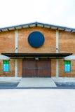 Väggen för röd tegelsten och den trästor dörren för fönster och i tappning utformar Arkivfoto