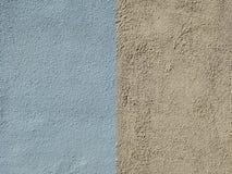 Väggen täckas med blått och guling texturerad murbruk royaltyfri fotografi
