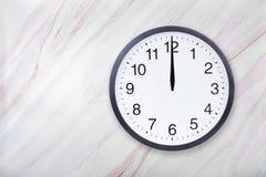 Väggklocka på marmortexturshow tolv klockan Middagar eller midnatt för kontorsklockashow arkivbild