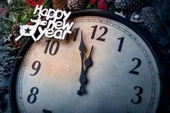 Väggklockan i garneringar för jul eller för nytt år slås in med granfilialer och julpynt På klockan royaltyfri fotografi