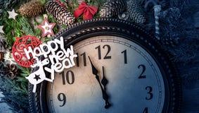 Väggklockan i garneringar för jul eller för nytt år slås in med granfilialer och julpynt På klockan arkivfoton
