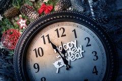 Väggklockan i garneringar för jul eller för nytt år slås in med granfilialer och julpynt På klockan arkivbild