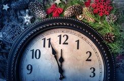 Väggklockan i garneringar för jul eller för nytt år slås in med granfilialer och julpynt På klockan royaltyfria bilder