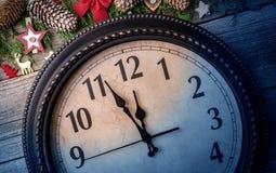 Väggklockan i garneringar för jul eller för nytt år slås in med granfilialer och julpynt På klockan arkivfoto