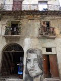VÄGGMÅLNING AV EN KVINNA PÅ DEN FÖRFALLNA FASADEN, HAVANNACIGARR, KUBA Royaltyfri Bild