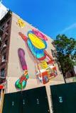 Väggmålning av OS Gemeos i i stadens centrum Manhattan, NYC Arkivbild