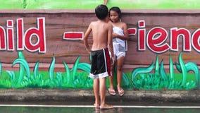 Väggmålningen målade konkreta skolaväggen är ett ställe var två barn tycker om regnbadet stock video