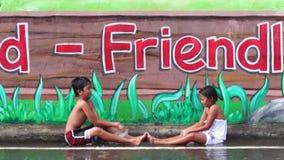Väggmålningen målade konkreta skolaväggen är ett ställe var två barn tycker om regnbadet arkivfilmer