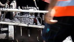Väghyvelgrävskopaspridning den krossade stenen på vägen lager videofilmer