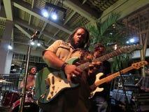 Vägledningsmusikbandet sitter fast på gitarren och trummar på etapp på Mai Tai Bar Royaltyfri Foto