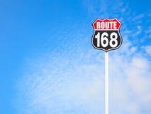 Vägmärke för tappningrutt 168 och blå himmel Arkivbild